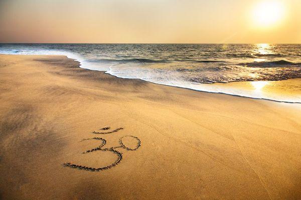 Sanskrit Om symbol sand beach ocean