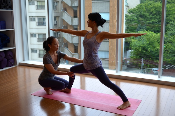 Senior Be Yoga Japan Instructor, Chiharu Ueyama, adjusting Warrior II pose, Hiroo, Tokyo, Japan