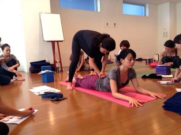 Kumiko Mack adjusting backbend pose at 500 hour Teacher Training Course at Be Yoga Japan, Hiroo, Tokyo
