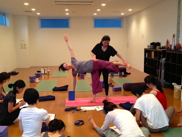 Kumiko Mack adjusting standing pose at 500-hour Teacher Training Course at Be Yoga Japan, Hiroo, Tokyo